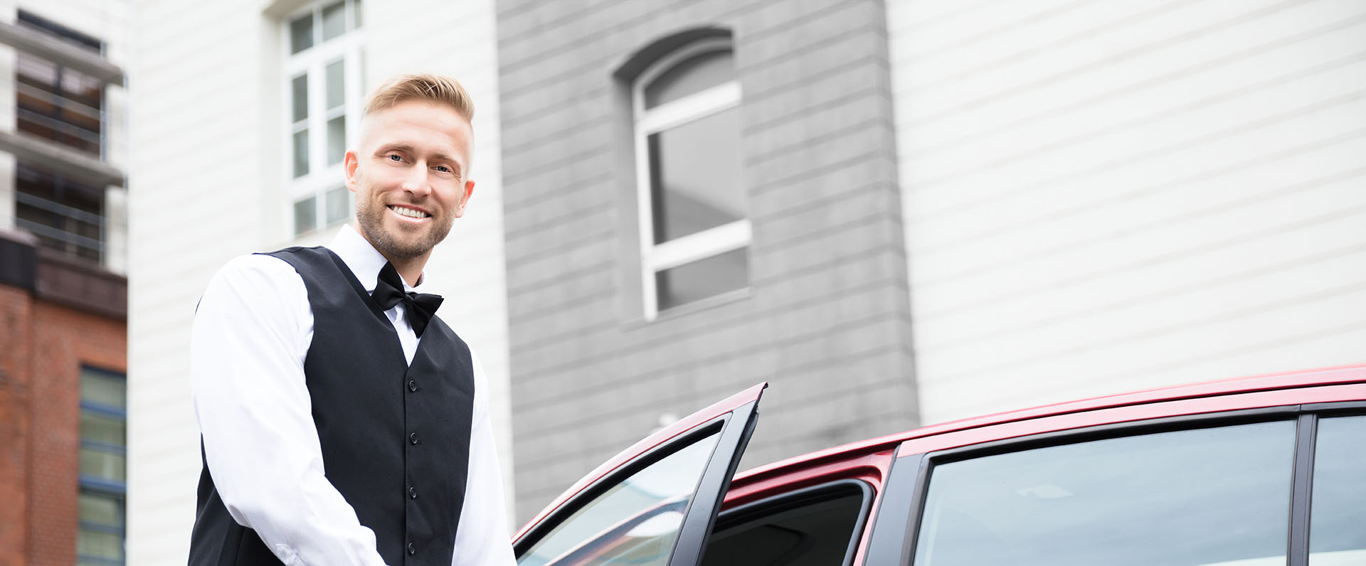 smiling valet opening a car door for his client