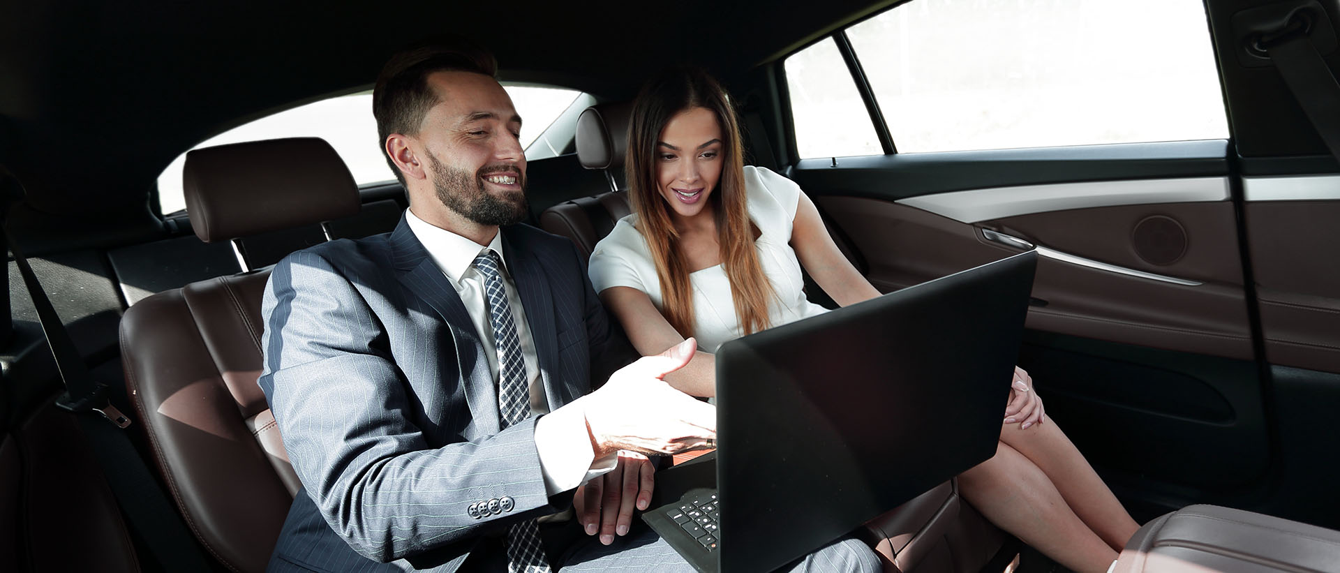 a man and a woman inside a car working on a laptop computer